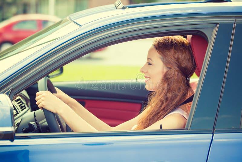 Glückliche schöne junge Frau, die ihr neues blaues Auto fährt lizenzfreie stockfotos