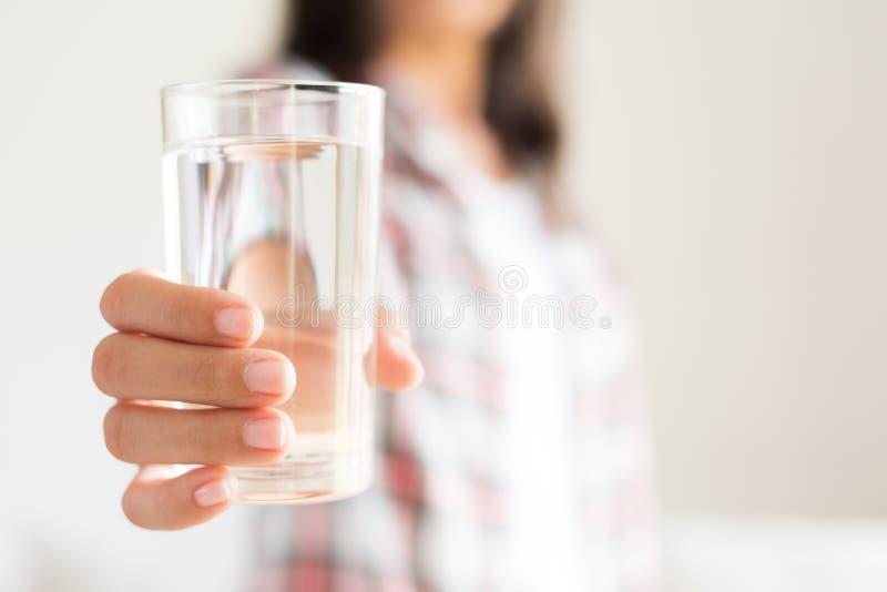 Glückliche schöne junge Frau, die Trinkwasser Glas hält stockfoto