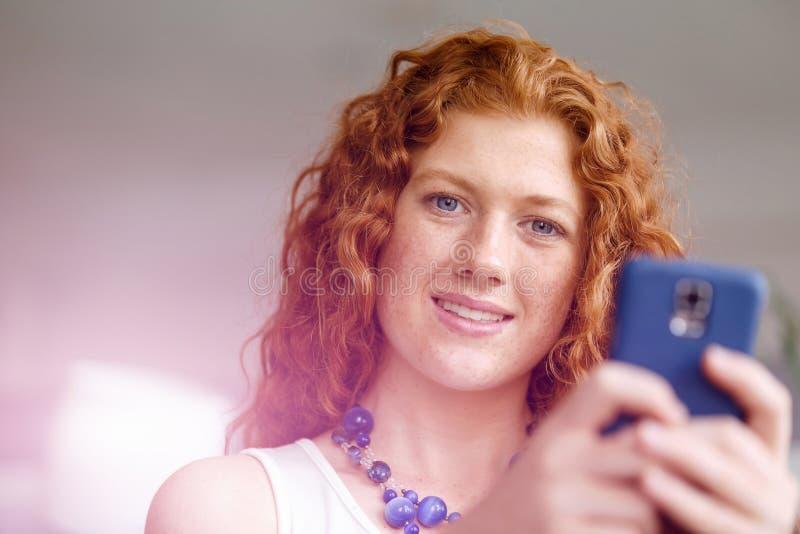 Glückliche schöne junge Geschäftsfrau, die das intelligente Telefonlächeln verwendet lizenzfreie stockbilder