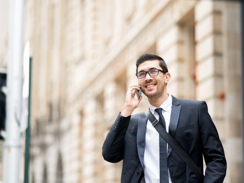Glückliche schöne junge Geschäftsfrau, die das intelligente Telefonlächeln verwendet lizenzfreies stockbild