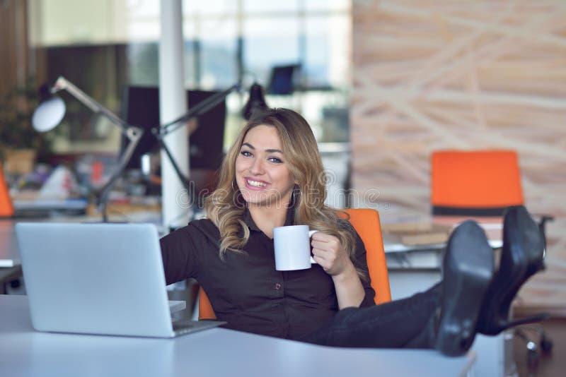 Glückliche schöne junge Geschäftsfrau, die am Handy im Büro sitzt und spricht stockfotografie