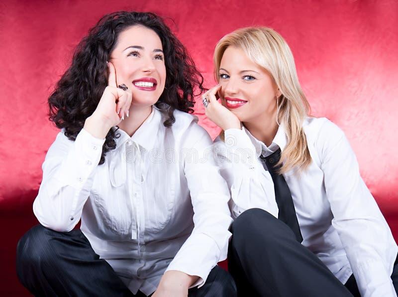 Glückliche schöne junge lachende und aufwerfende Frauen lizenzfreie stockbilder