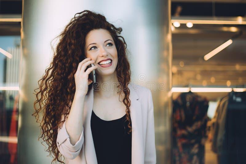Glückliche schöne junge Rothaarigefrau, die das Einkaufen und das Sprechen tut stockbilder