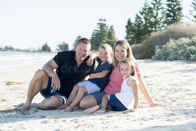 Glückliche schöne kaukasische Familie, die Feiertage auf dem Strand lächelt mit der Mutter und Vater sitzen auf Sand mit kleinem  lizenzfreie stockbilder