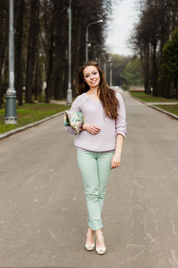 Glückliche schöne lächelnde Ausstattung der Frau in Mode auf weißem und grünem Hintergrund lizenzfreie stockfotos