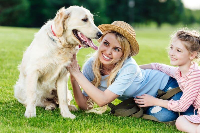glückliche schöne Mutter und Tochter, die Hund beim Lügen auf grünem Gras betrachtet lizenzfreie stockfotos