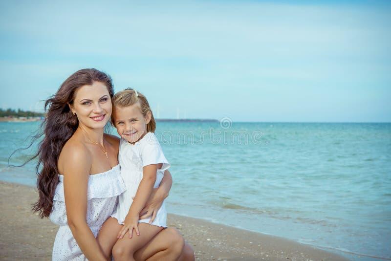 Glückliche schöne Mutter und Tochter, die Strandzeit genießt stockfoto