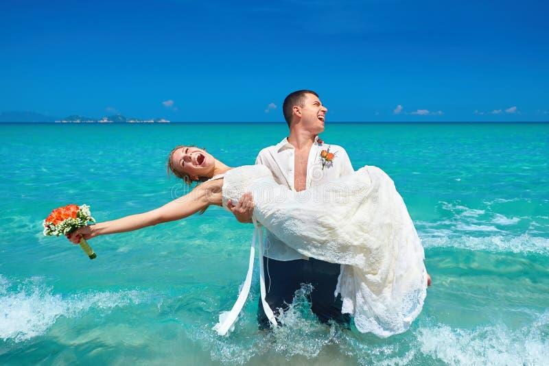 Glückliche schöne Paare auf dem Strand im Hochzeitskleid stockbilder