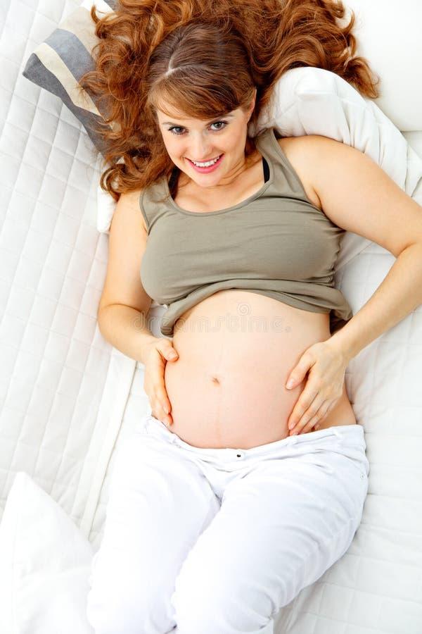 Glückliche schöne schwangere Frau, die auf Couch sich entspannt stockfotografie