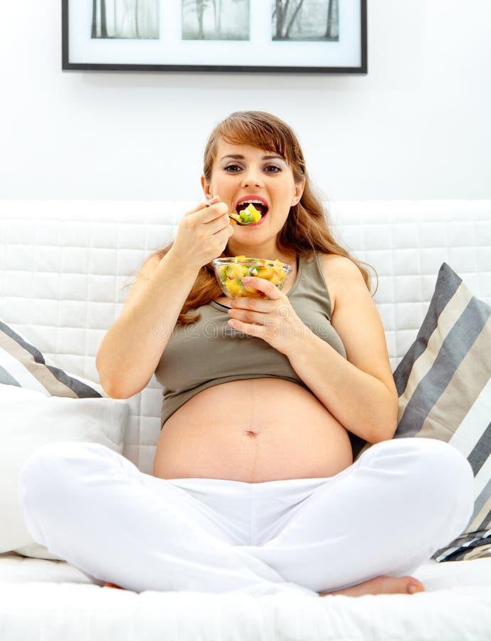 Glückliche schöne schwangere Frau, die Fruchtsalat isst stockbilder