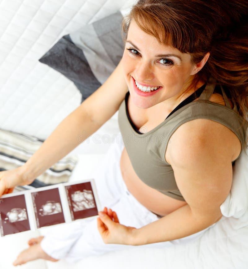 Glückliche schöne schwangere Frau mit Echo in den Händen lizenzfreie stockfotografie