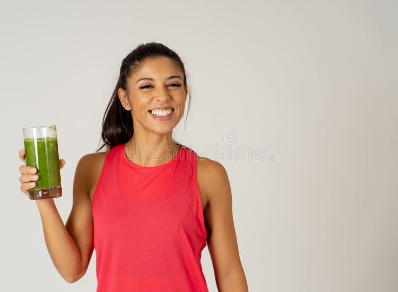 Glückliche schöne Sitzsportfrau, die gesunden Frischgemüse Smoothie lächelt und trinkt lizenzfreie stockbilder
