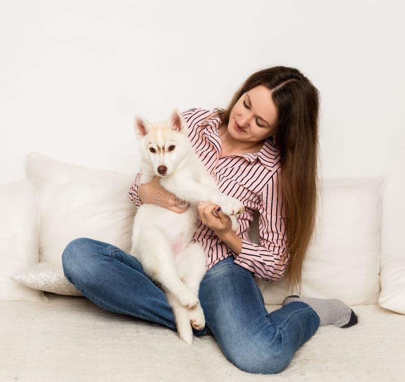 Glückliche Schönheit, die auf einer Couch mit ihrem Haustier stillsteht Mädchen, das Welpenschlittenhund umarmt stockfoto