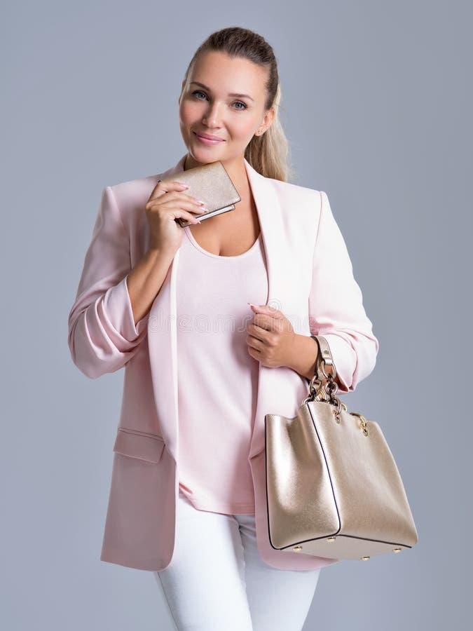 Glückliche Schönheit mit Handtasche und Geldbörse im Einkaufen stockfoto