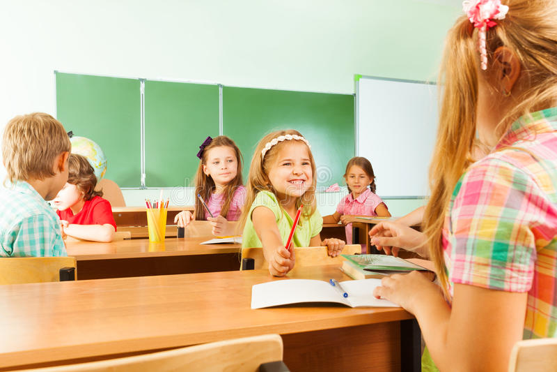 Glückliche Schüler im Klassenzimmer, das an den Schreibtischen sitzt stockfotografie