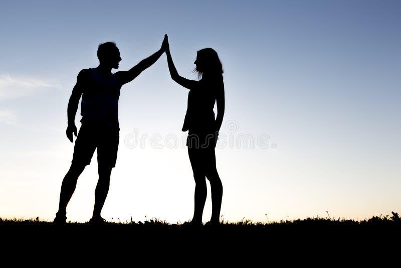 Glückliche Schattenbildpaare, die Hände gegen den Himmel an der Dämmerung halten stockfoto