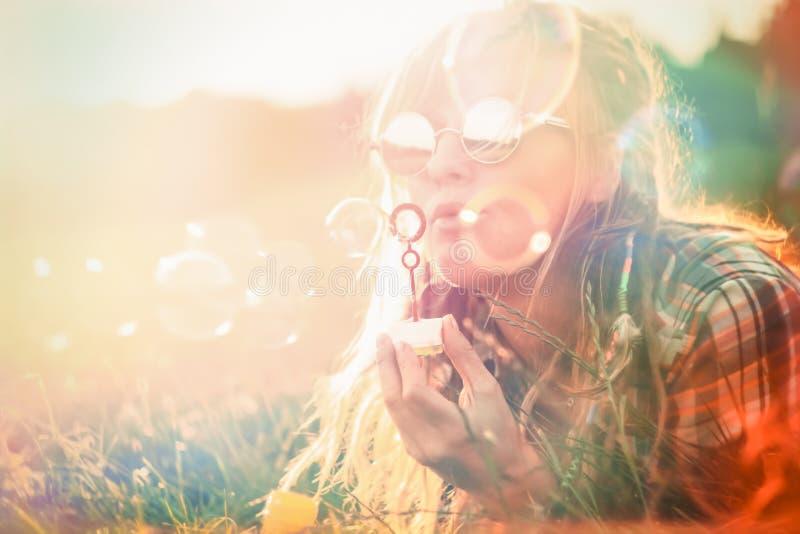 Glückliche Schlagseifenblasen der jungen Frau stockfotos