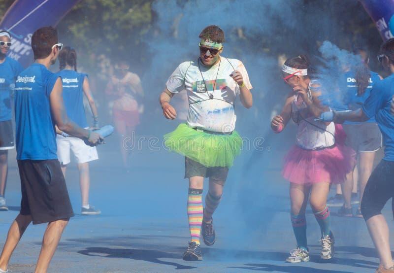 Glückliche schmutzige Leute, die am Farblauf laufen stockbilder