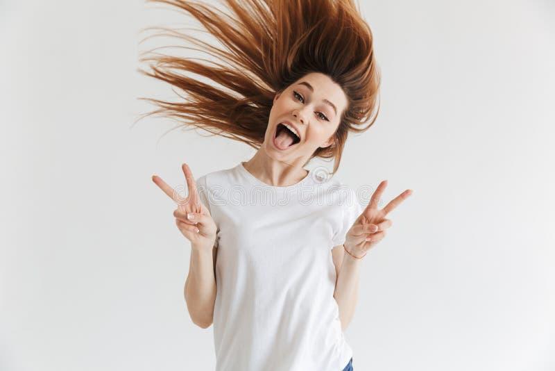 Glückliche schreiende Frau im T-Shirt, das Frieden zeigt, gestikuliert stockfoto