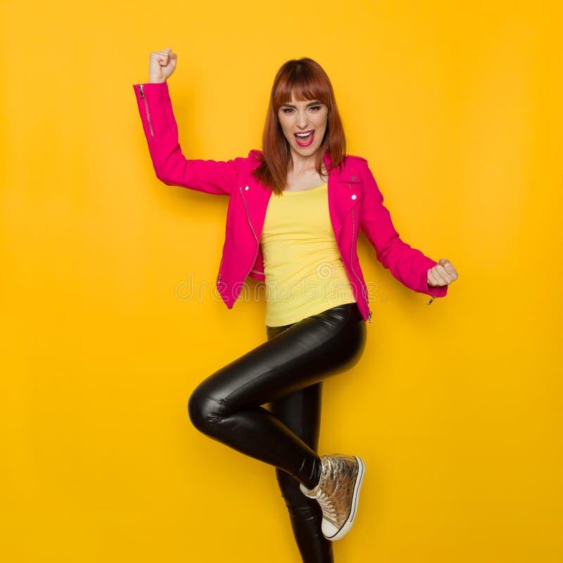 Glückliche schreiende junge Frau in der rosa Jacke steht auf einem Bein lizenzfreies stockbild