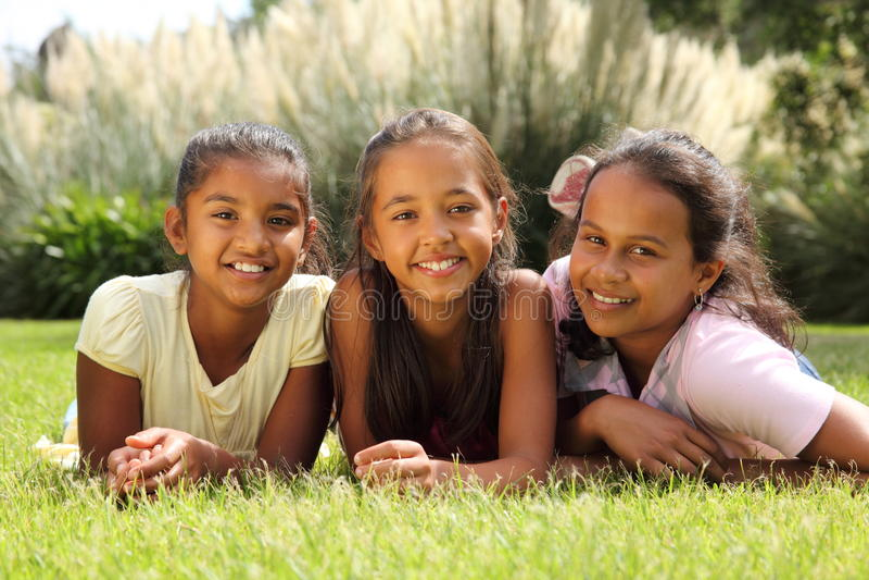 Glückliche SchuleFreundinnen, die zusammen im Gras liegen stockfoto