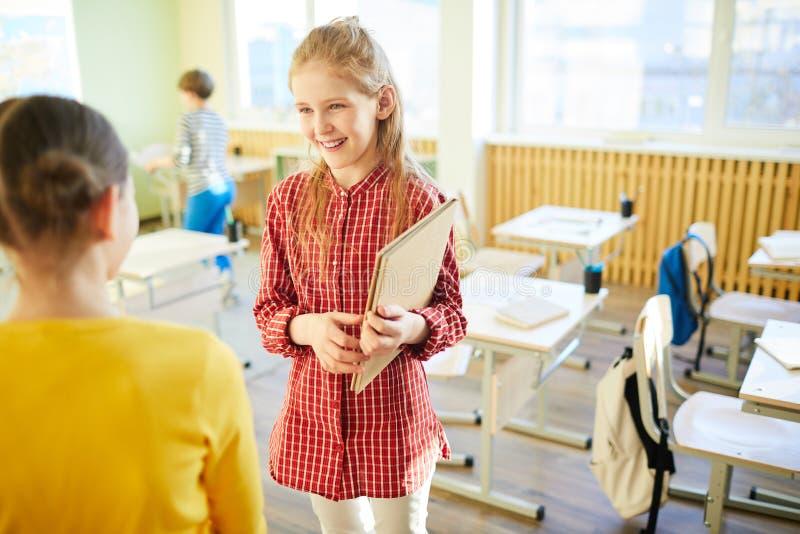 Glückliche Schulfreunde, die im Klassenzimmer sprechen lizenzfreies stockbild