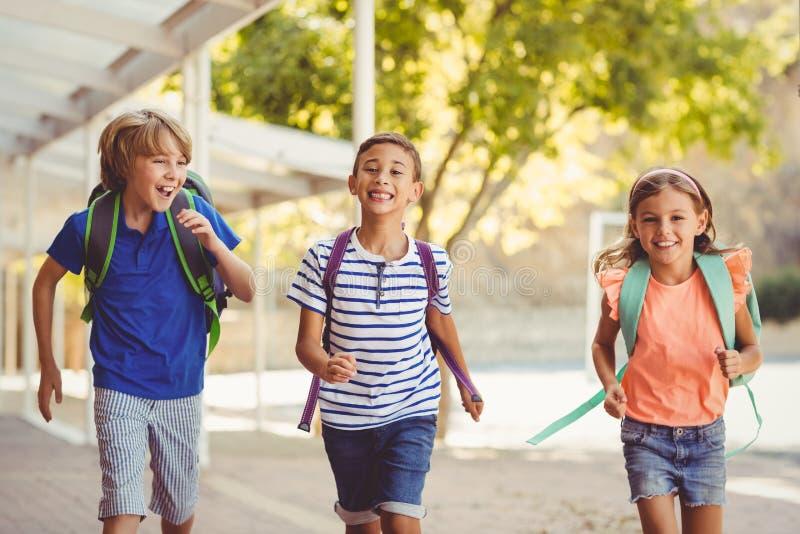 Glückliche Schulkinder, die in Korridor laufen stockfoto