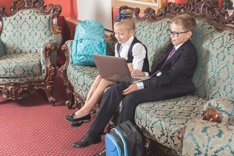 Glückliche Schulkindergebrauchs-Laptop-Computer Angekleidet in den Schulklagen stockfotos