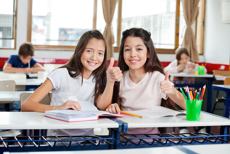 Glückliche Schulmädchen, die oben Daumen am Schreibtisch gestikulieren stockfotografie