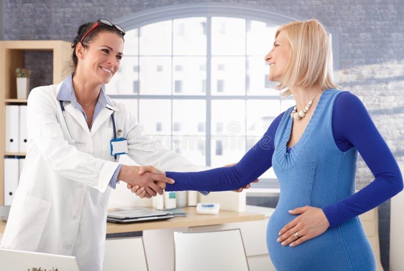 Glückliche schwangere Frau in der Arztpraxis stockfotos