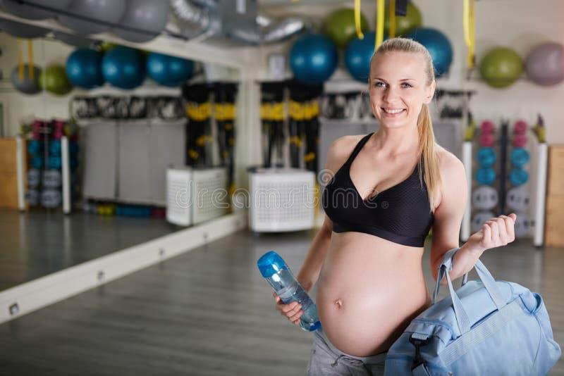 Glückliche schwangere Frau an der Turnhalle, die Sport Tasche und bidon hält lizenzfreies stockbild