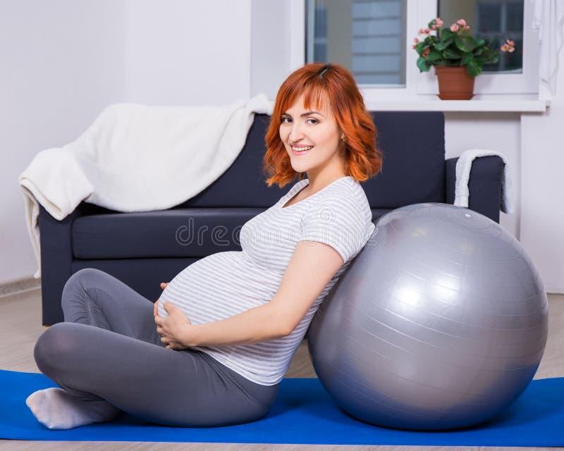 Glückliche schwangere Frau, die Übungen mit fitball im Wohnzimmer tut lizenzfreies stockfoto