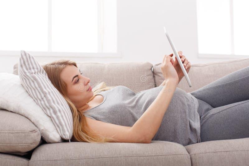 Glückliche schwangere Frau, die digitale Tablette verwendet lizenzfreie stockbilder