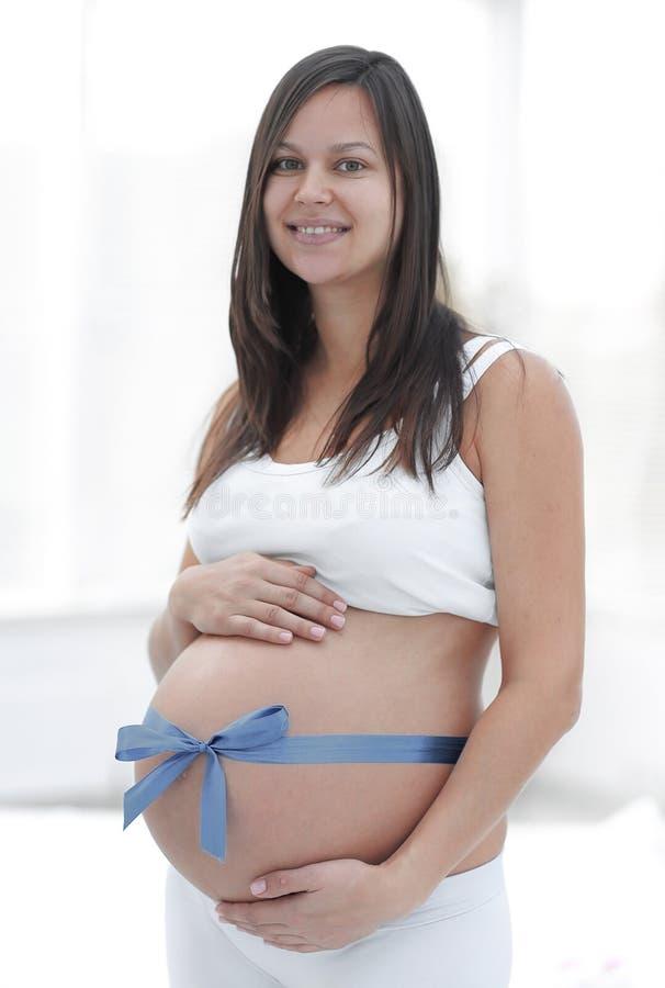 Glückliche schwangere Frau, die ihren Bauch und Taille misst stockfotos