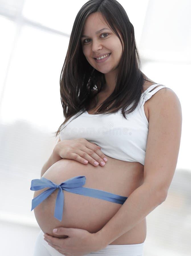 Glückliche schwangere Frau, die ihren Bauch und Taille misst lizenzfreie stockfotos