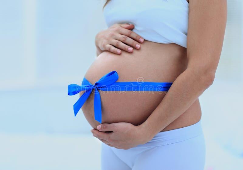Glückliche schwangere Frau, die ihren Bauch und Taille misst lizenzfreie stockfotografie