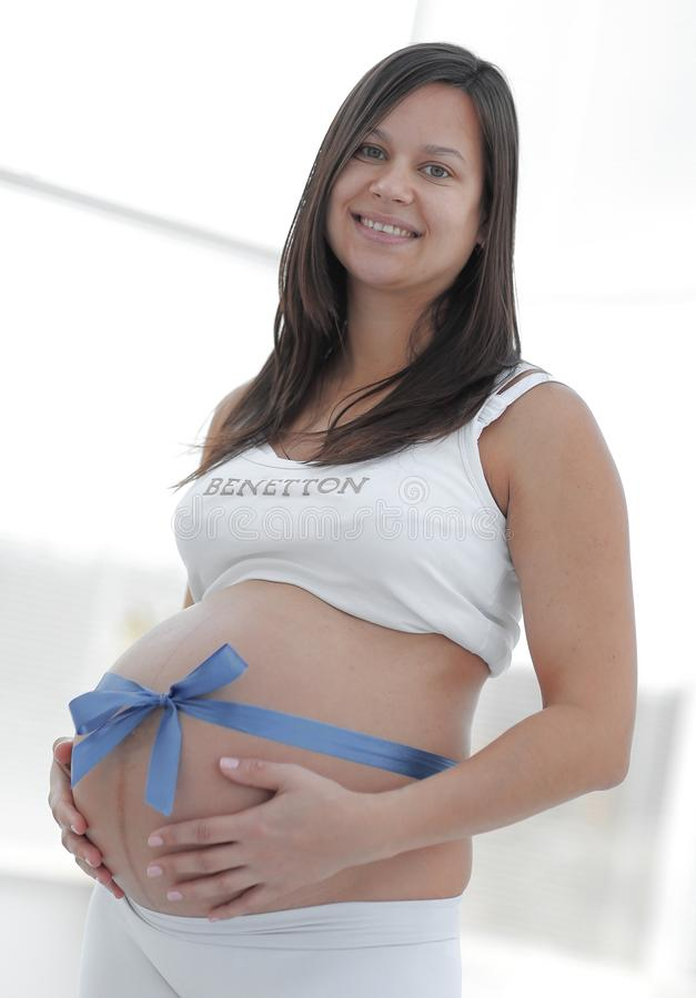 Glückliche schwangere Frau, die ihren Bauch und Taille misst lizenzfreies stockbild