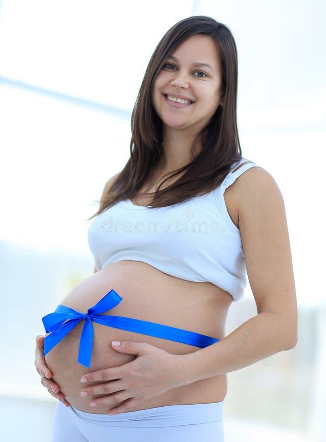 Glückliche schwangere Frau, die ihren Bauch und Taille misst lizenzfreies stockfoto