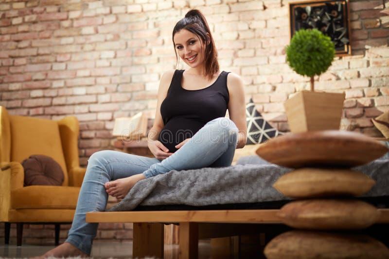 Glückliche schwangere Frau, die zu Hause auf Bett sitzt stockfoto