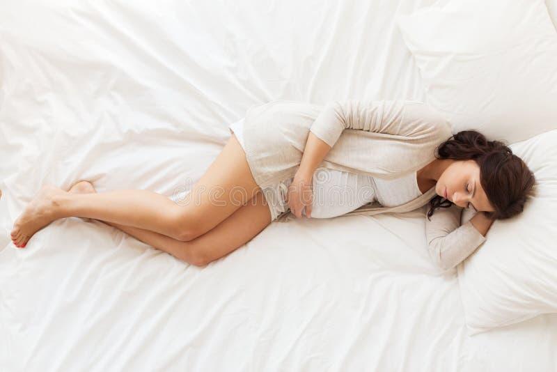 Glückliche schwangere Frau, die zu Hause im Bett schläft stockfotografie