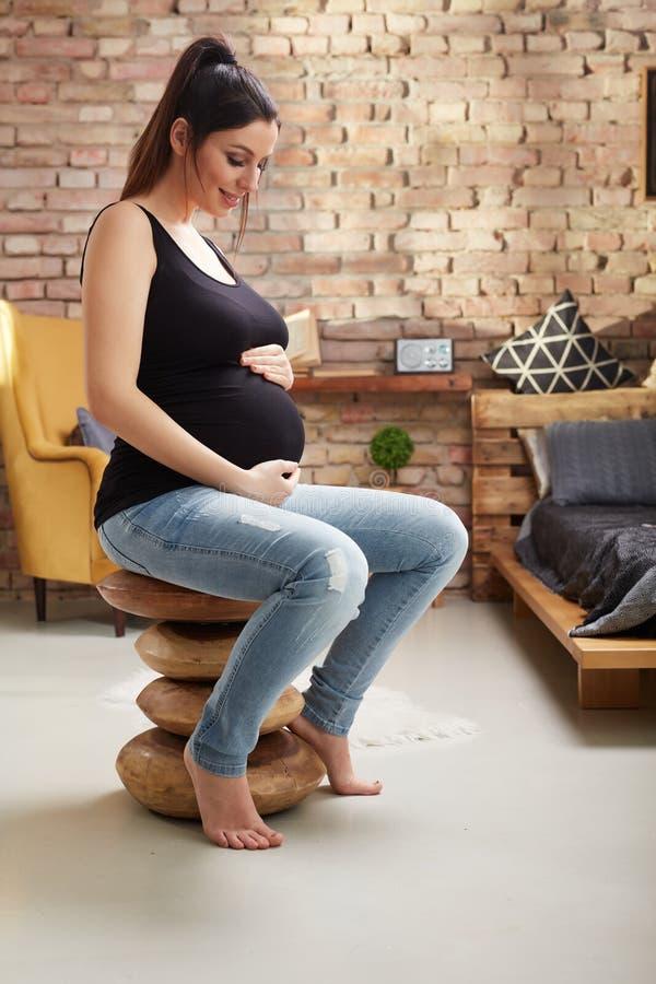 Glückliche schwangere Frau, die zu Hause sitzt stockfotos