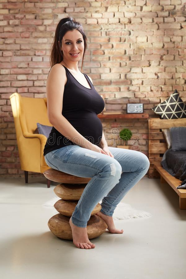 Glückliche schwangere Frau, die zu Hause sitzt stockbilder