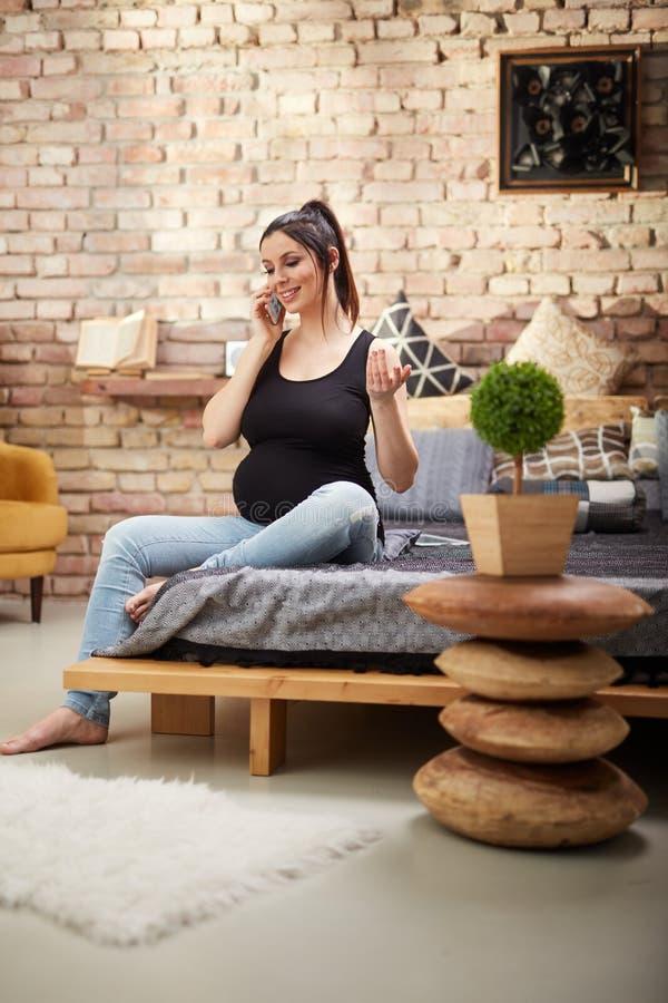 Glückliche schwangere Frau, die zu Hause sitzt stockfoto