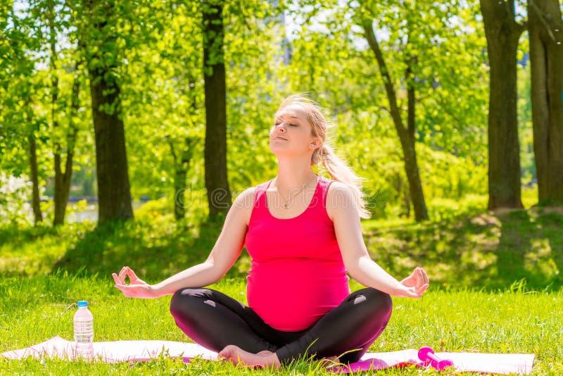 Glückliche schwangere Frau in einem Lotussitz, der Yoga tut stockbilder