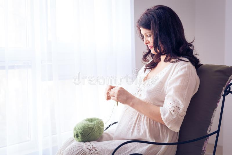 Glückliche schwangere Frau im weißen Kleiderstricken lizenzfreie stockfotografie