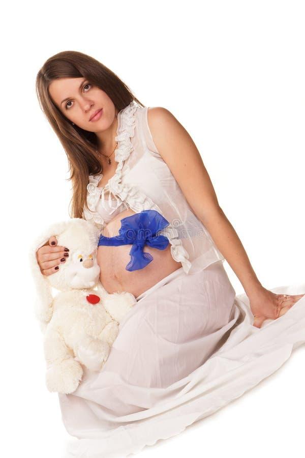 Glückliche schwangere Frau mit dem Bauch mit blauem Bogen lizenzfreie stockfotos