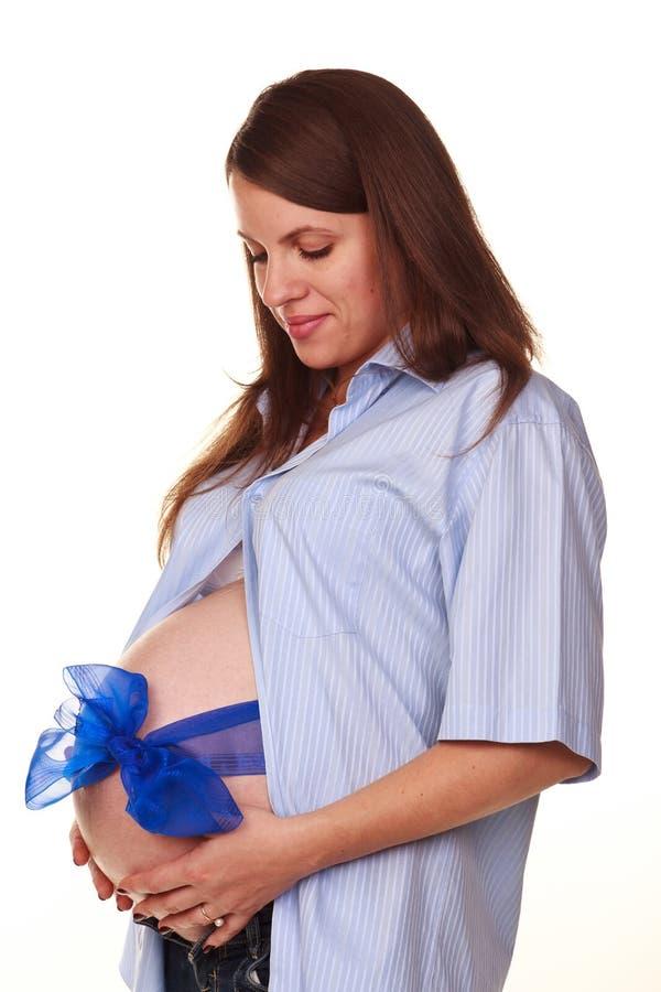 Glückliche schwangere Frau mit dem Bauch mit blauem Bogen stockfoto