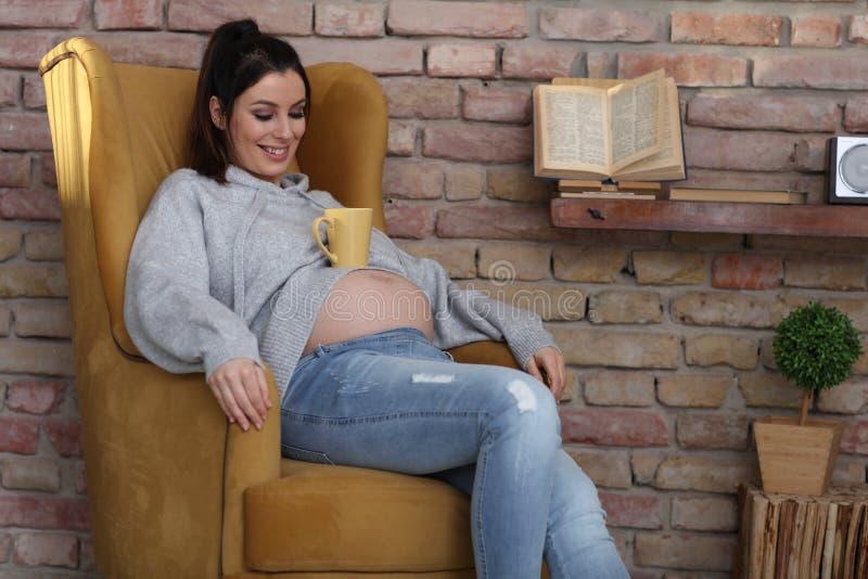 Glückliche schwangere Frau zu Hause, die im Lehnsessel sich entspannt lizenzfreie stockfotos