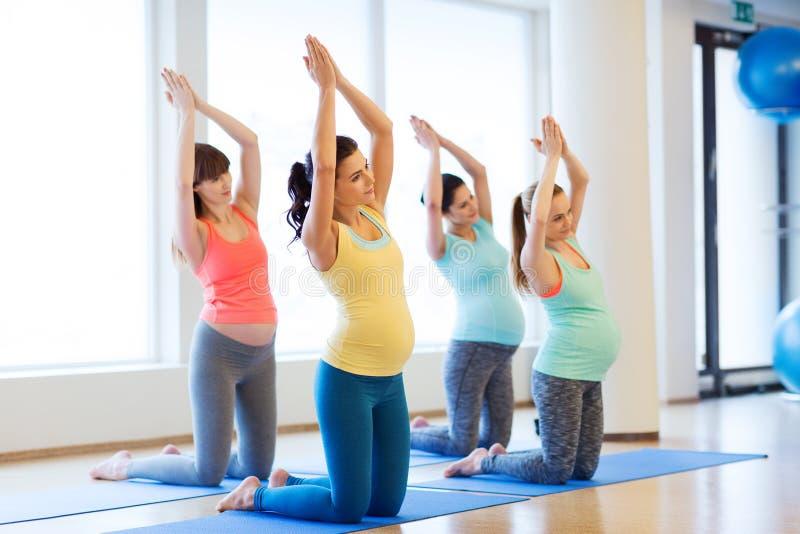 Glückliche schwangere Frauen, die auf Matten in der Turnhalle trainieren stockfoto