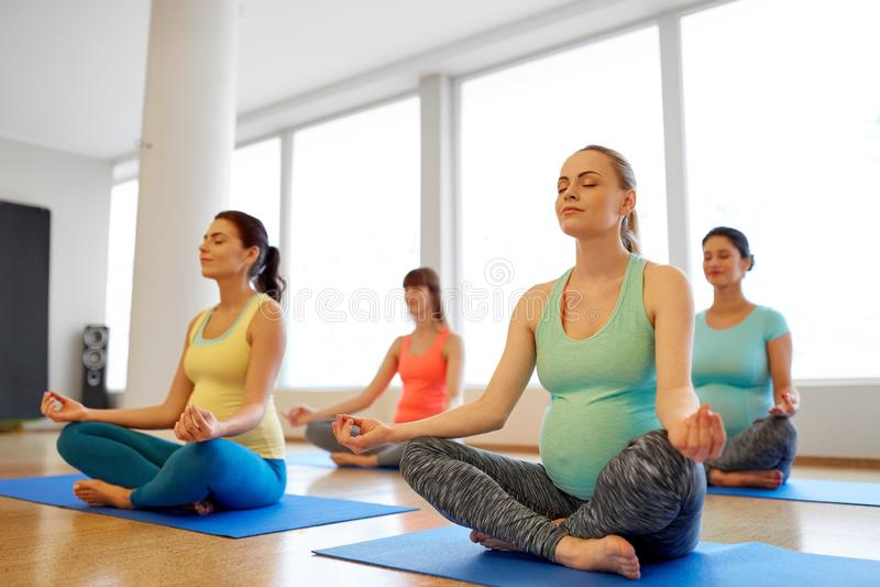 Glückliche schwangere Frauen, die am Turnhallenyoga meditieren stockfoto